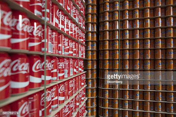 Cans of Coke and orange Fanta soft drink sit stacked on pallets in a storage area following manufacture at the CocaCola Co factory in Dongen...