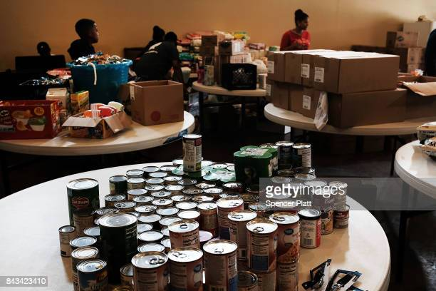 Cans of food are displayed on a table at a church that is now a relief center for flood victims in Orange as Texas slowly moves toward recovery from...