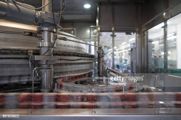Cans of softdrink cans pass along a conveyor during filling inside the Refresco Group NV beverage bottling factory in Maarheeze Netherlands on...