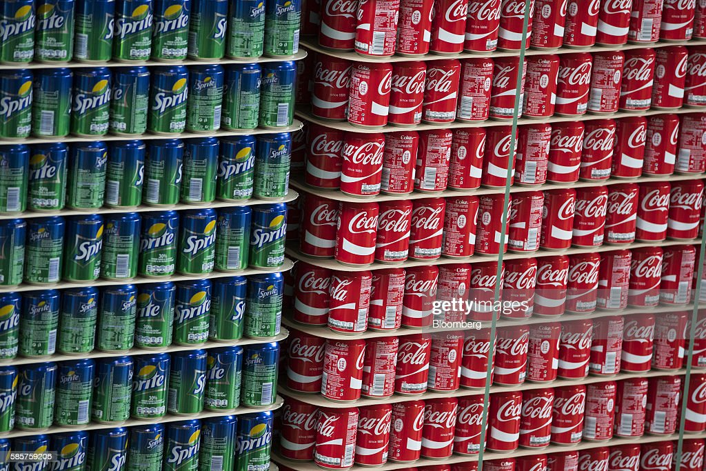 Cans of Sprite and Coke soft drink sit stacked on pallets in