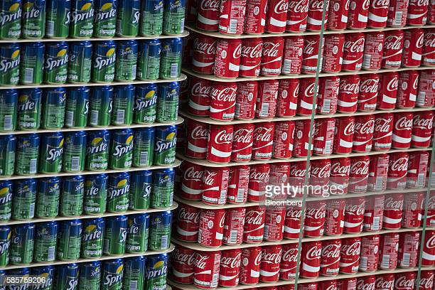 Cans of Sprite and Coke soft drink sit stacked on pallets in a storage area following manufacture at the CocaCola Co factory in Dongen Netherlands on...