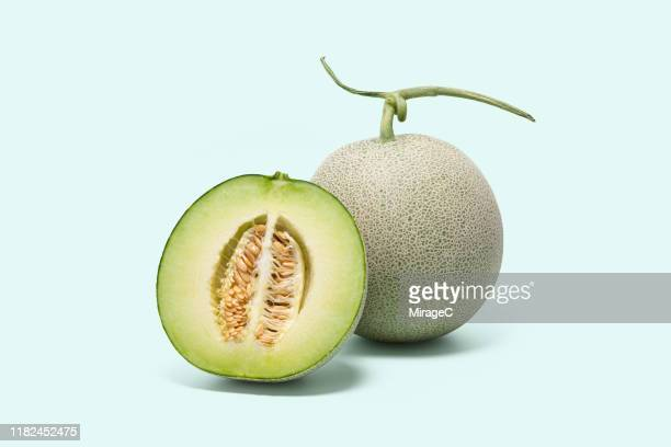 cantaloupe and cross section on colored background - muskmelon stock pictures, royalty-free photos & images