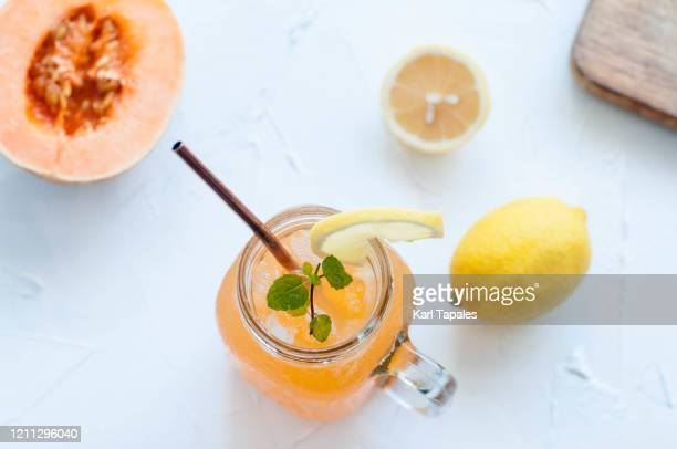 cantaloupe and lemon mock-tail on a white table - トロピカルフルーツ ストックフォトと画像