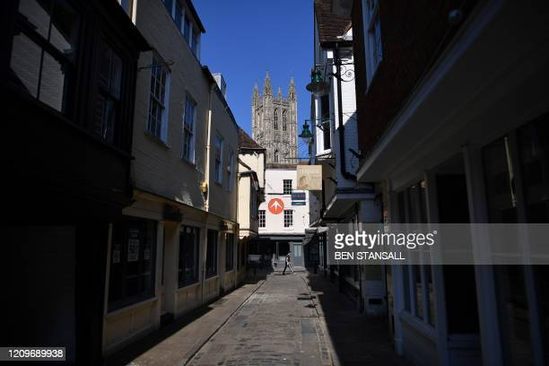 Canterbury Cathedral is pictured at the end of a deserted street in Canterbury south east England on April 11 as life in Britain continues over the...