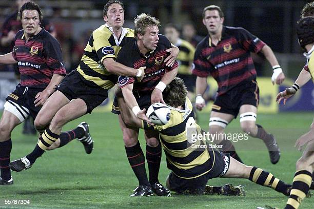 Canterbury halfback Justin Marshall is caught by Taranaki's Mark Urwin left and Brent Thompson during their Ranfurly Shield and Air New Zealand first...