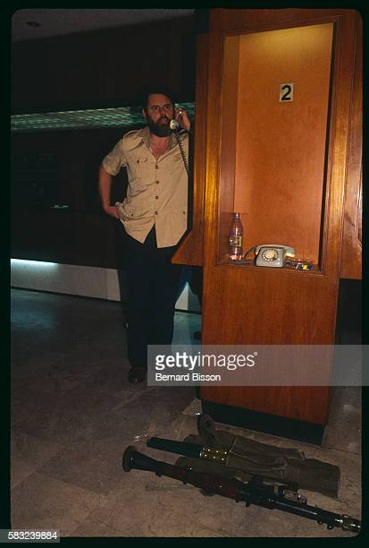 Canterbury's archbishop special hostage negotiator Terry Waite at a phone booth in the hall of the Commodore hotel, with a rocket launcher at his...