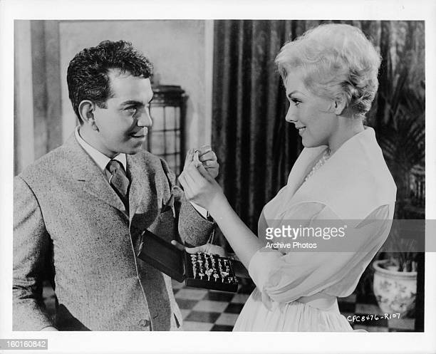 Cantinflas and Kim Novak exchanging item in a scene from the film 'Pepe' 1960