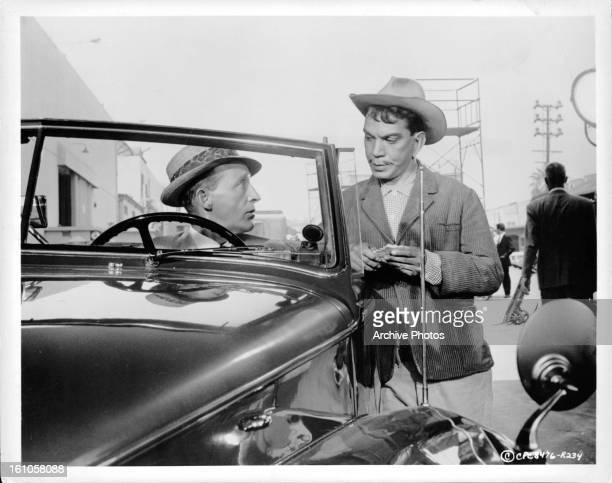 Cantinflas talks to a man in a car in a scene from the film 'Pepe' 1960