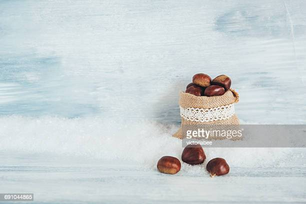canvas bag with fresh chestnuts - fake snow stock pictures, royalty-free photos & images