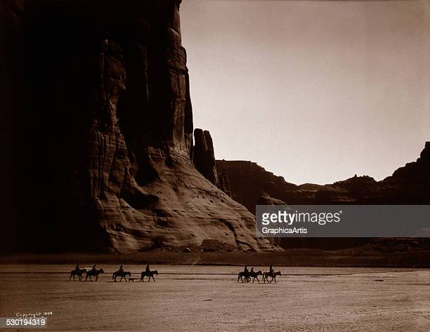 Canyon de Chelly Navajo by Edward S Curtis depicting Navajo riders and their dogs moving across the Canyon de Chelly in Arizona 1904 The work was...