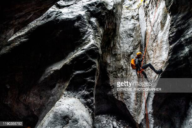 a canyoneering male making an abseil down the static rope into a dark stone cave - extreme sports stock pictures, royalty-free photos & images