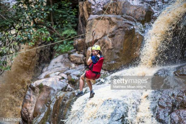 canyoning is one of the most popular activities in dalat. a girl ziplines down a waterfall. - danger stock pictures, royalty-free photos & images