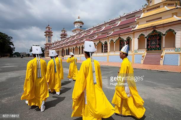 cao dai priests, cao dai temple. near ho chi minh. vietnam - hugh sitton fotografías e imágenes de stock