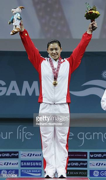 Cao Lei of China celebrates on to the podium with her gold medal at the victory ceremony for the Women's 75kg Weightlifting Group A Final during the...