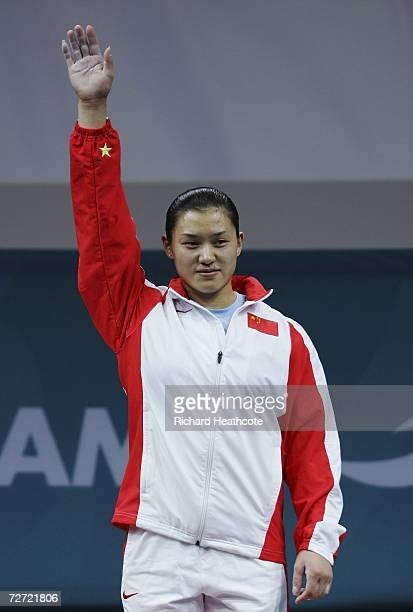 Cao Lei of China steps on to the podium to collect her gold medal at the victory ceremony for the Women's 75kg Weightlifting Group A Final during the...