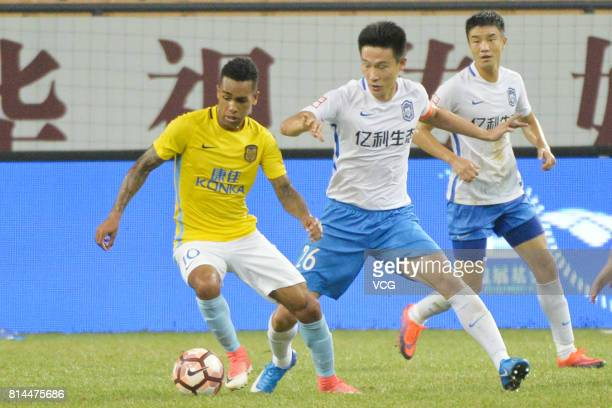 Cao Yan of Tianjin Teda and Alex Teixeira of Jiangsu Suning compete for the ball during 2017 Chinese Super League 17th round match between Tianjin...