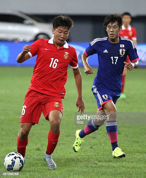 Cao Yongjing of China vies with Takagi Akito of Japan during a match between China and Japan of 2015 'Changan Ford Cup' CFA International Youth...