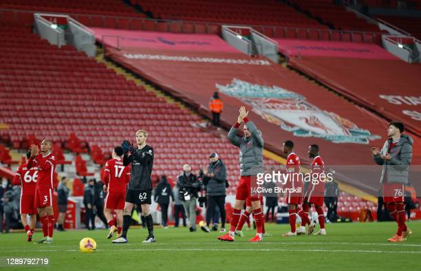 Caoimhin Kelleher and Jordan Henderson of Liverpool along with team mates applaud the few fans allowed in the Kop after the Premier League match...