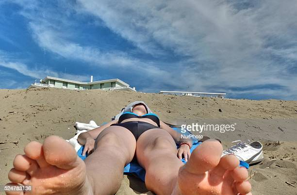 Caorle Veneto Italy May 2014 Early spring seazon at the Adriatic Sea beach in Caorle resort Young lady lays on the sandy beach and sunbathing Visible...
