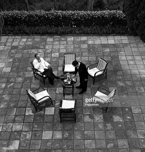 Cap Ferrat France English author Somerset Maugham is pictured with his secretarycompanion as they take cocktails before dinner on the terrace at the...