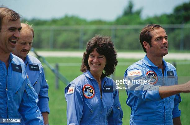 astronaut Sally Ride walks with Robert Crippen and other astronauts in a field prior to the launch of the Space Shuttle Challenger's second mission...