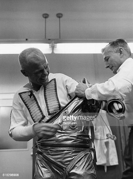 Cape Canaveral FLAstronaut John Glenn smiles happily while he is assisted by suit technician Joe Schmitt in preparing for the MercuryAtlas 6 flight...