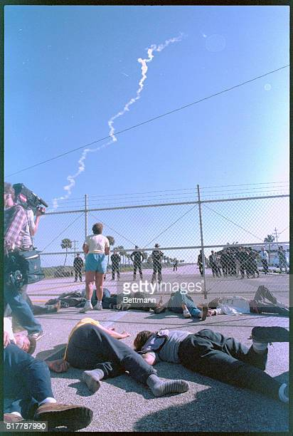 Pretending to be dead in a nuclear blast several antinuclear weapons protesters lie in the road before the main gate at Cape Canaveral Air Force...