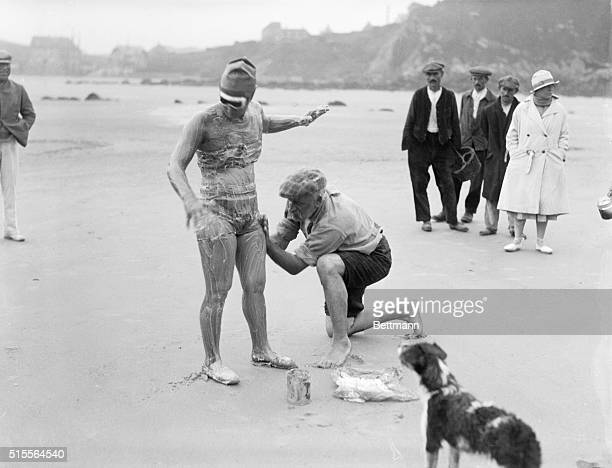 Trainer Bill Burgers greasing Gertrude Ederle on the beach at Cape Griz Nez France for her attempt to conquer the English Channel