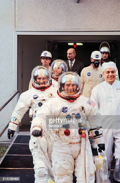 Apollo 12 astronauts walk out of building in which they were suited up and head for transfer van prior to moon blastoff First is Charles Conrad...