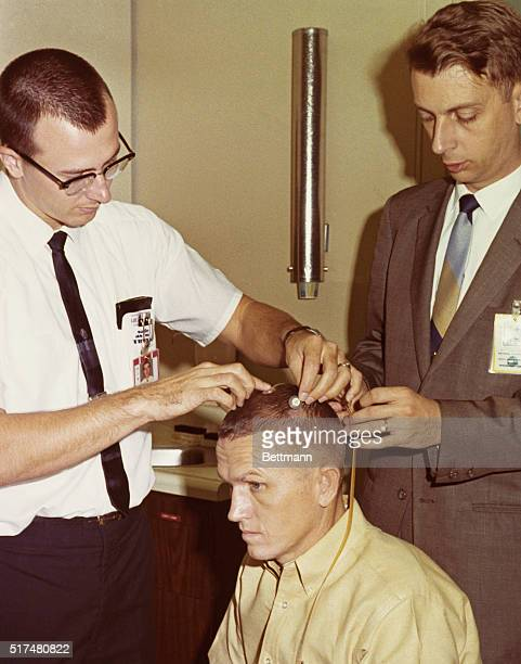 Cape Kennedy Florida Astronauts Frank Borman Gemini 7 command pilot grimaces as one of two scalp electrodes is attached to his head electrodes is...