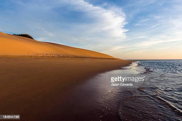 A calm sea laps the shore of a coastal desert sand dune at sunset.