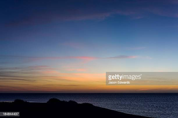 A sunset afterglow silhouettes a coastal sand dune by a tropical sea.