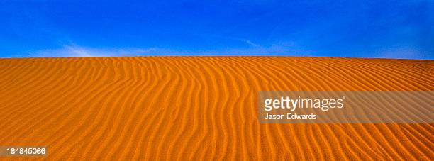 Geometric ripples in the face of a red sand dune in a coastal desert.