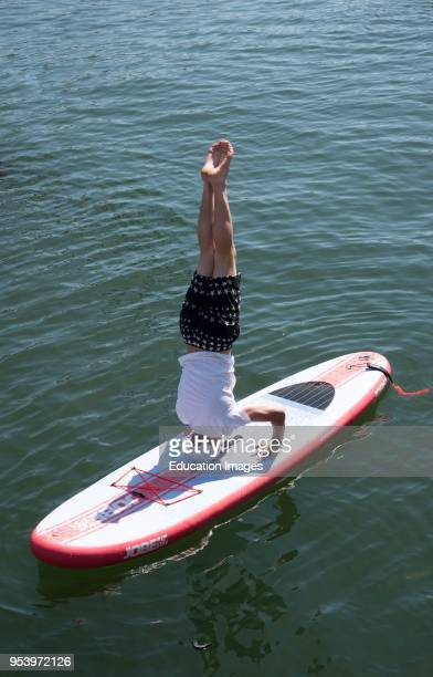 Cape Town harbour South Africa Paddle boarder performing a headstand