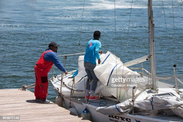 Cape Town harbour South Africa Volunteer instructor advising on raising the sail of a yacht to a young sailor