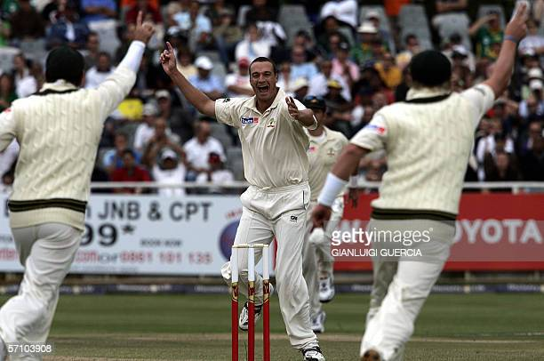 Australian bowler Stuart Clark celebrates with teammates the dismissal of South African batsman and Captain Graeme Smith 16 March 2006 during the day...