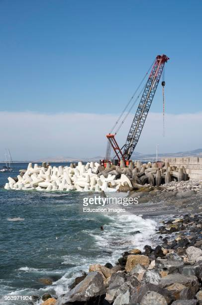 Cape Town South Africa Crane placing tetrapods concrete blocks to protect the sea wall around the harbour
