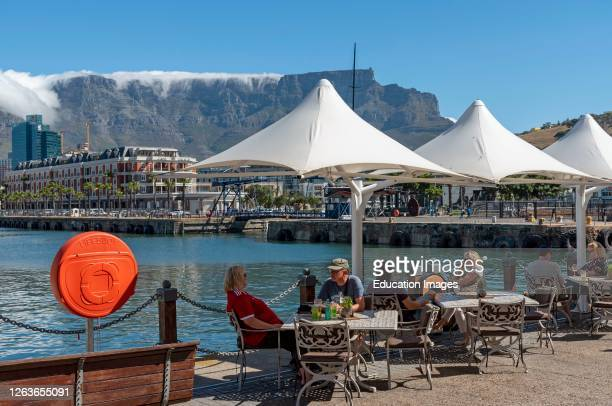 Cape Town, South Africa, Landscape view of the waterfront with tourists eating and drinking and cloud creeping over the summit of Table Mountain.