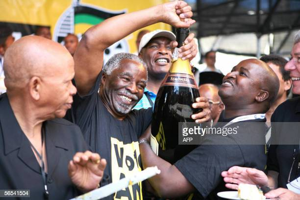 President Thabo Mbeki opens 08 January 2006 a bottle of champagne to mark the 94th anniversary celebration of the ANC in style at Athlone Stadium...