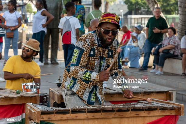 Cape Town, South Africa, Street musician in colorful clothing plays xylophone on the waterfront area of central Cape Town.