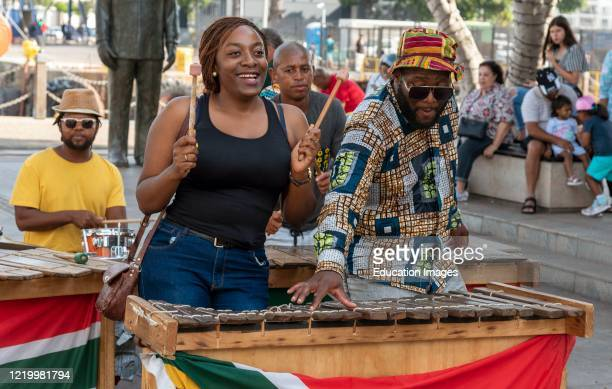Cape Town, South Africa, Street musicians having fun with tourists on the waterfront area of central Cape Town. Woman interacts with band.