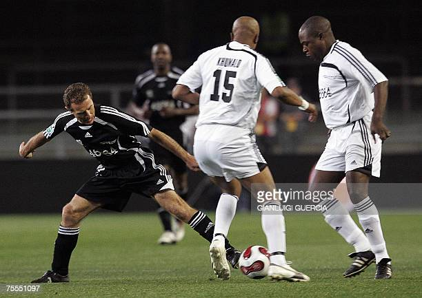 World XI Spanish midfielder Emilio Butragueno tries to break trough Africa XI Doctor Khumalo 18 July 2007 during the 90 minutes for Mandela match to...