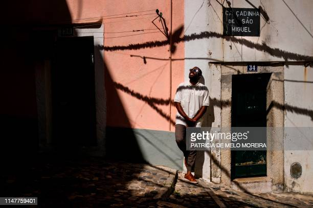 Cape Verdean Dino D'Santiago poses for a photo at the Alfama neighbourhood in Lisbon on May 20 2019 From fado sounds to Cape Verde mornas or bossa...