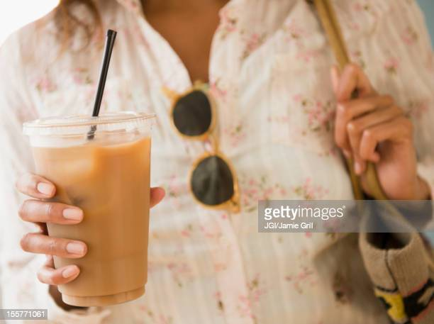 Cape Verdean woman drinking iced coffee