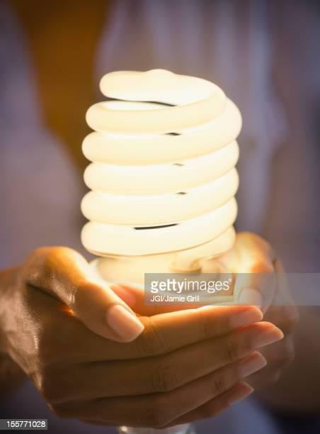 Cape Verdean woman holding CFL light bulb