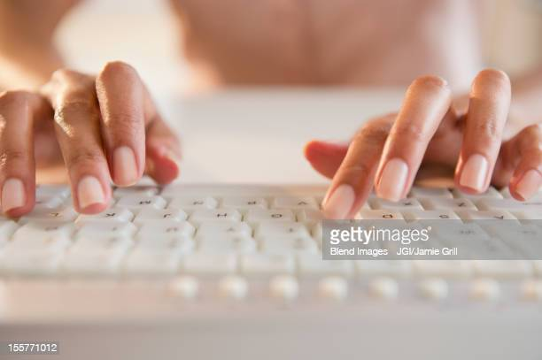 cape verdean woman typing on keyboard - computertoetsenbord stockfoto's en -beelden