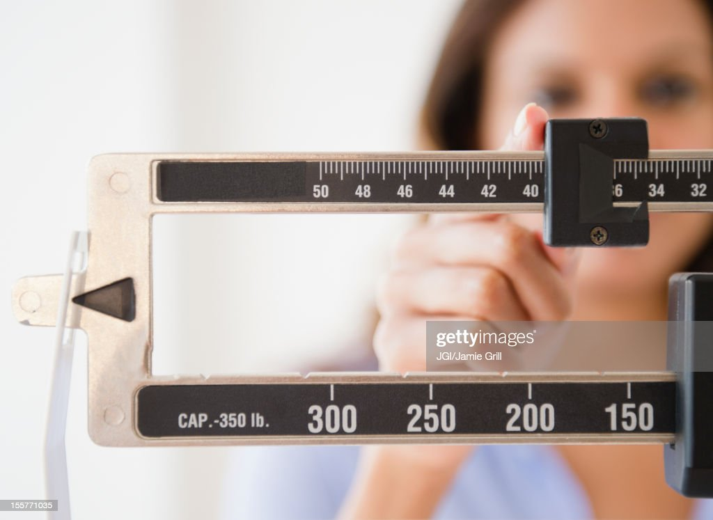 Cape Verdean woman weighing herself : Stock Photo