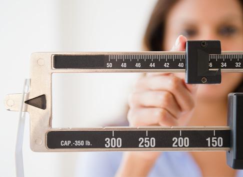 Cape Verdean woman weighing herself - gettyimageskorea