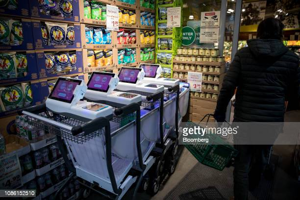 Caper Inc smart shopping carts sit at the entrance to a Foodcellar Co grocery store in the Long Island City neighborhood in the Queens borough of New...