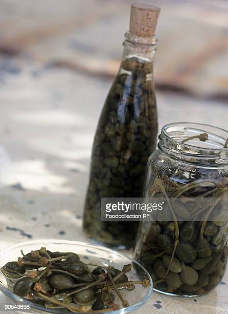 Capers on plate, in screw-top jar and in bottle